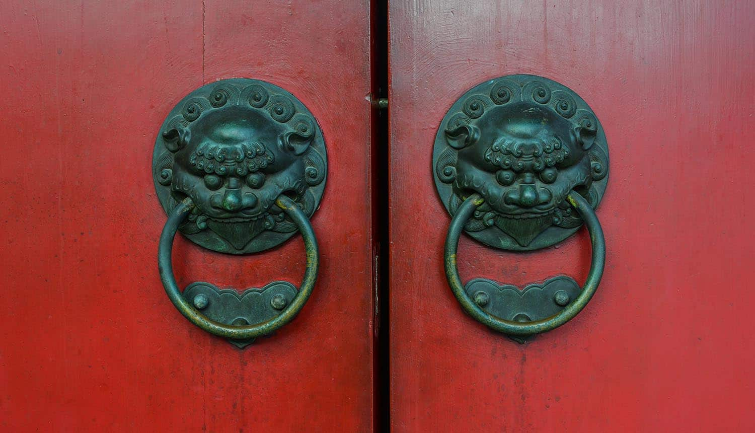 Old bronze knocker with red door in Chinese temple showing national security risks of Chinese tech companies