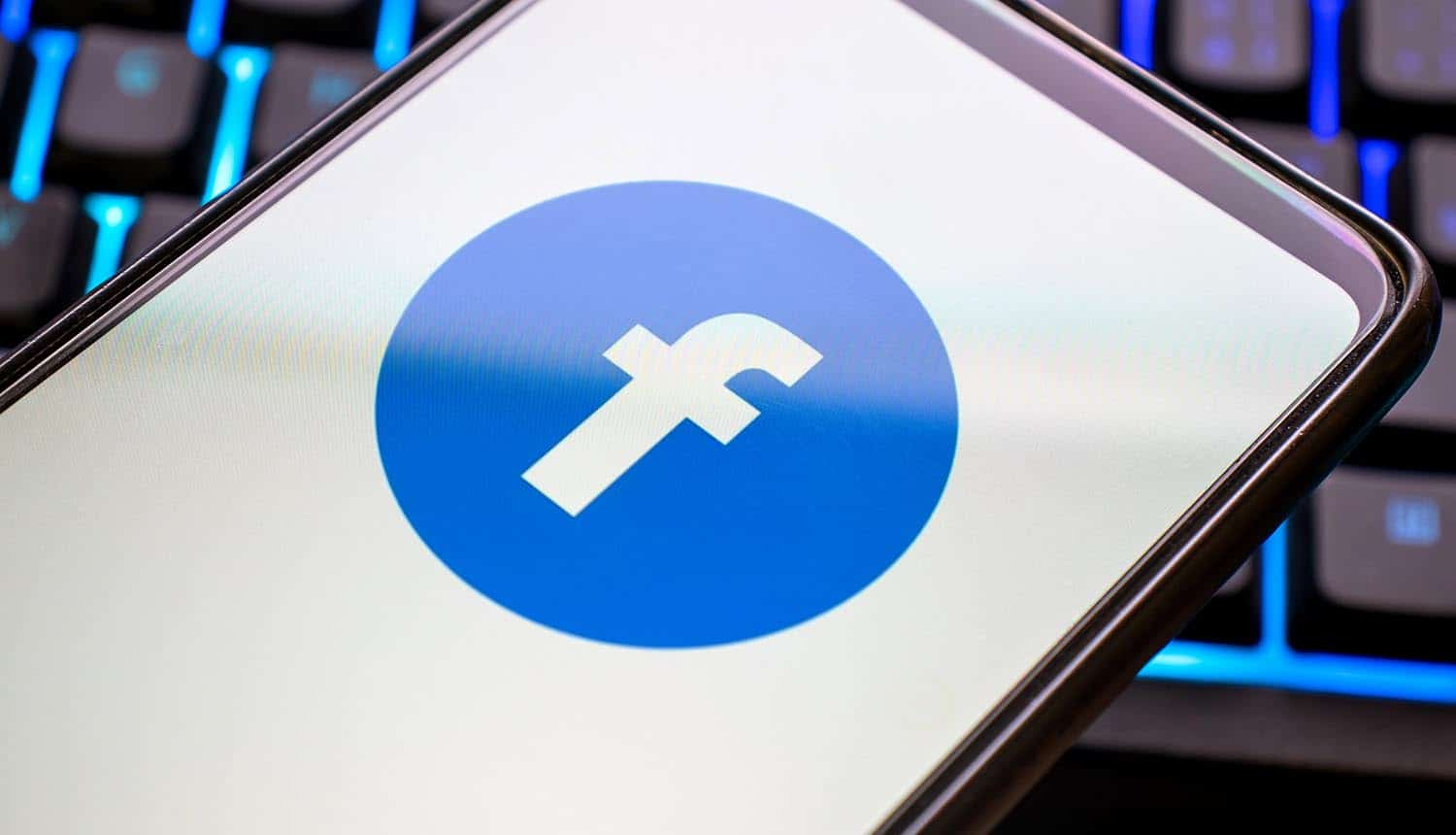 Mobile phone with blue facebook logo on display showing data protection commissioner directive to shut down Facebook Pages