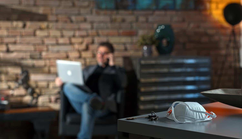 Businessman working at home leaving COVID-19 protective mask on desk showing digital risks
