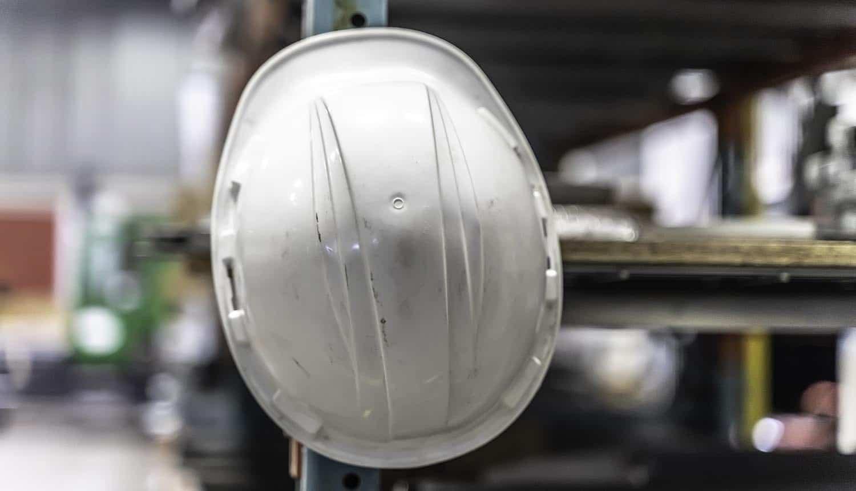 Safety hard hat helmet hanging on factory shelf showing OT security