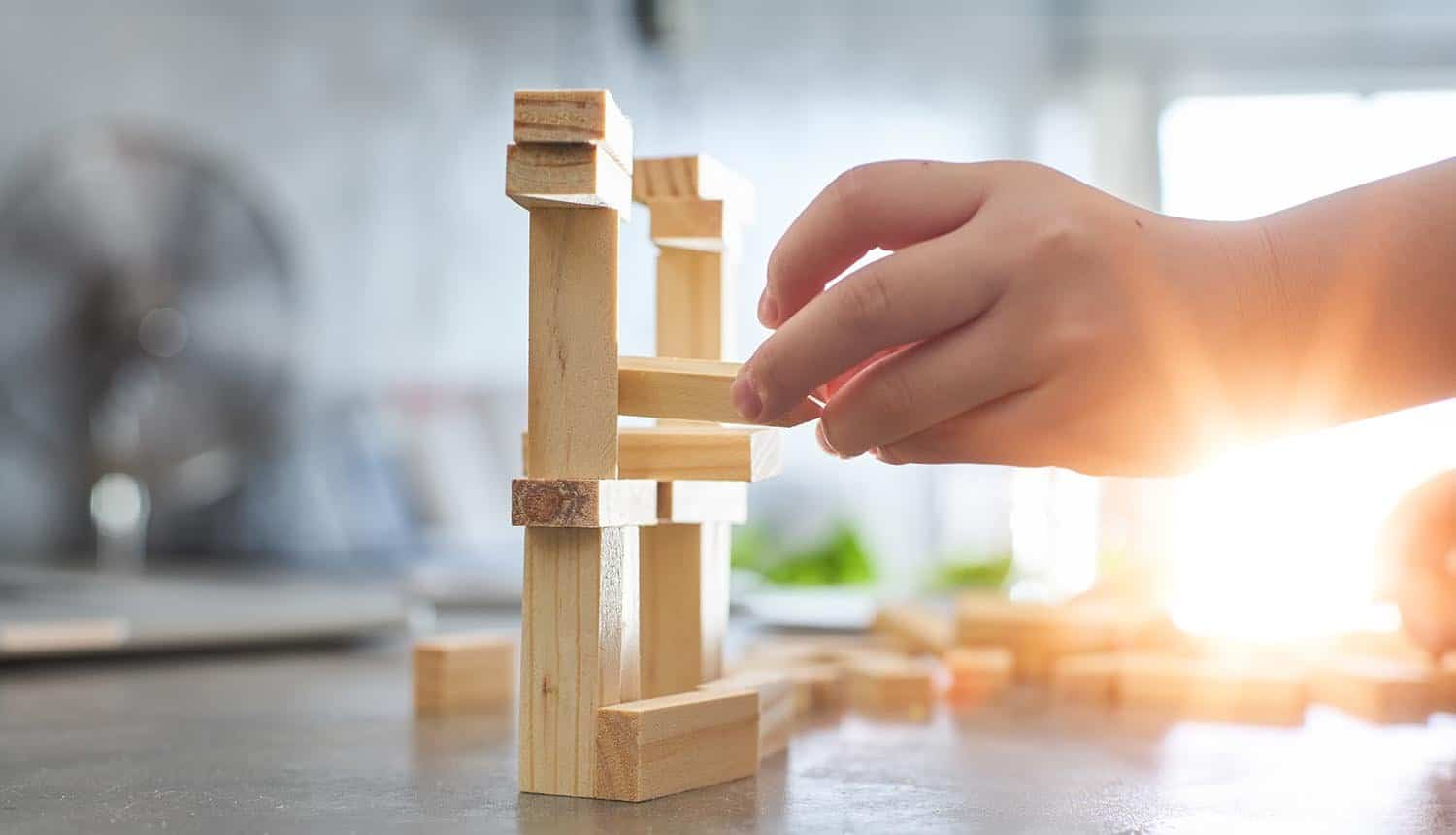 Hand of kid playing a blocks wood tower game showing third party risk