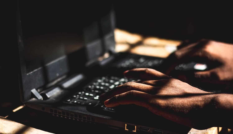 Hacker using laptop showing North Korea hackers exploiting VPN vulnerability