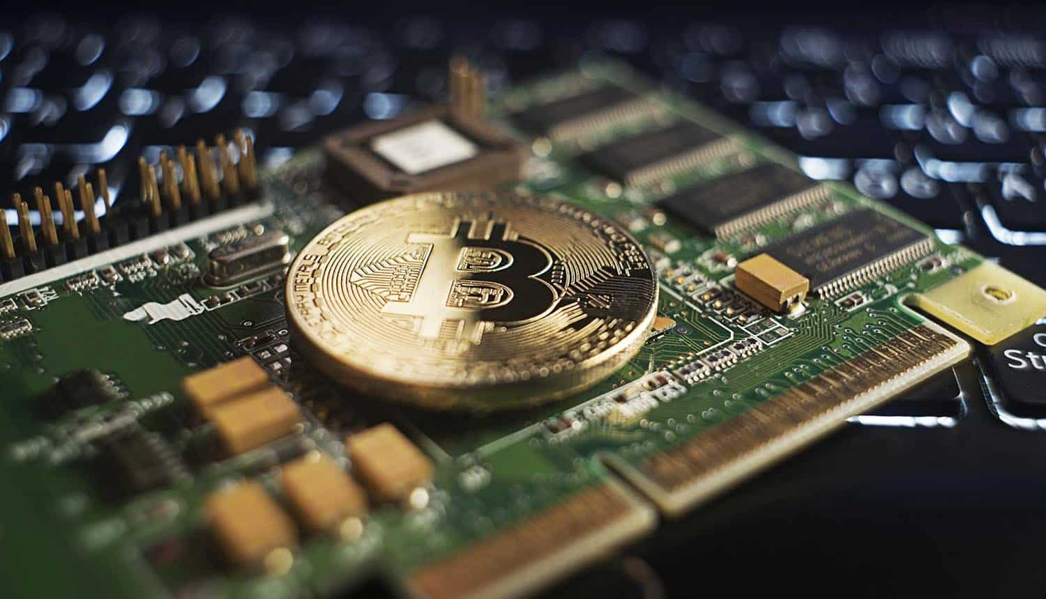 Golden coin with bitcoin symbol on a mainboard showing crypto mining scams in Android apps