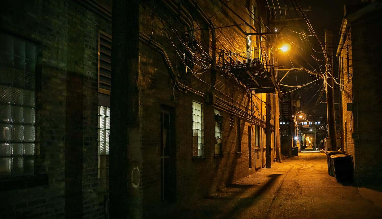 Vintage scary urban city alley at night showing REvil ransomware group retreating from dark web