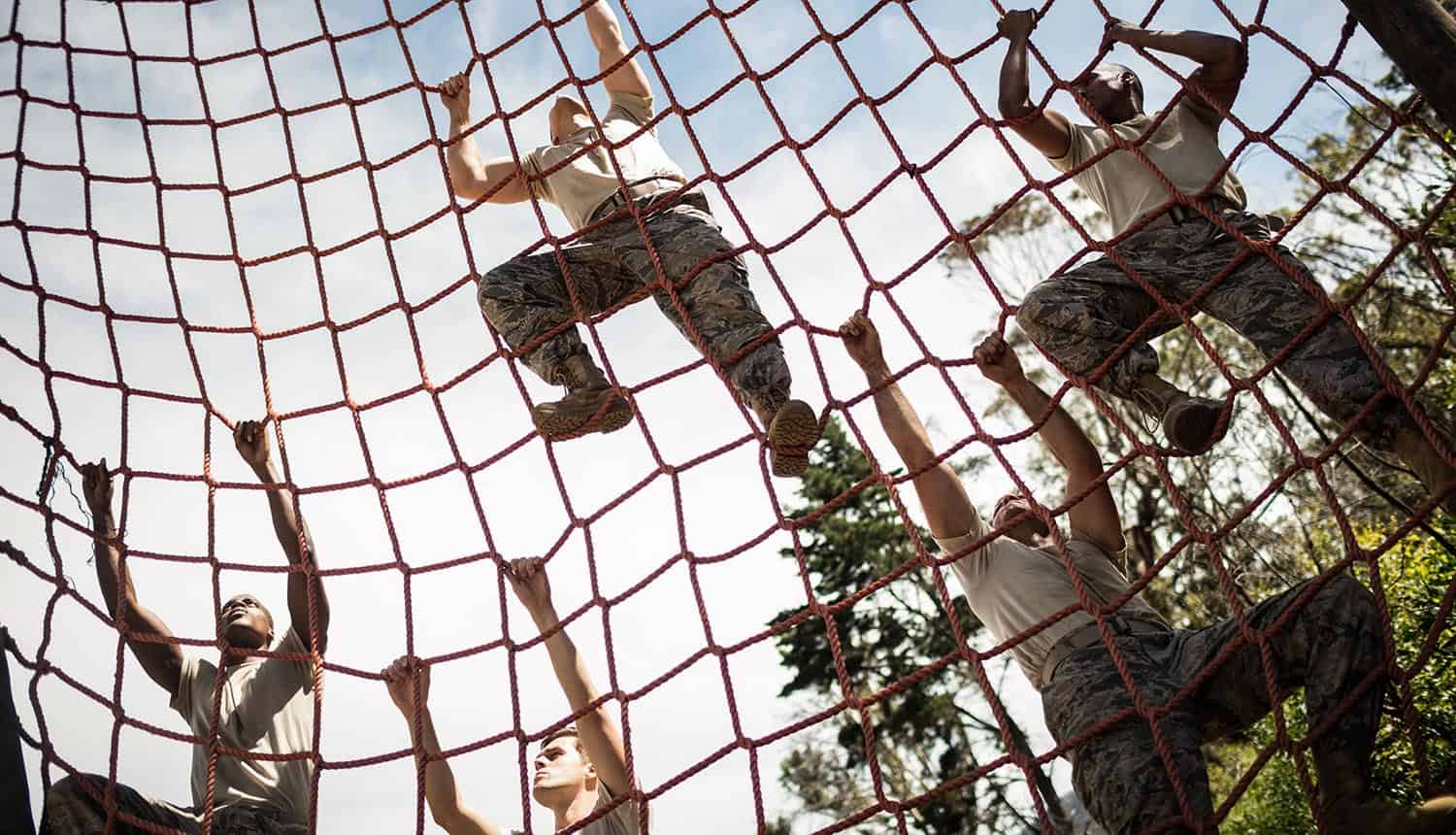 Military soldiers climbing rope during obstacle course showing defense contractors problem with CMMC requirements