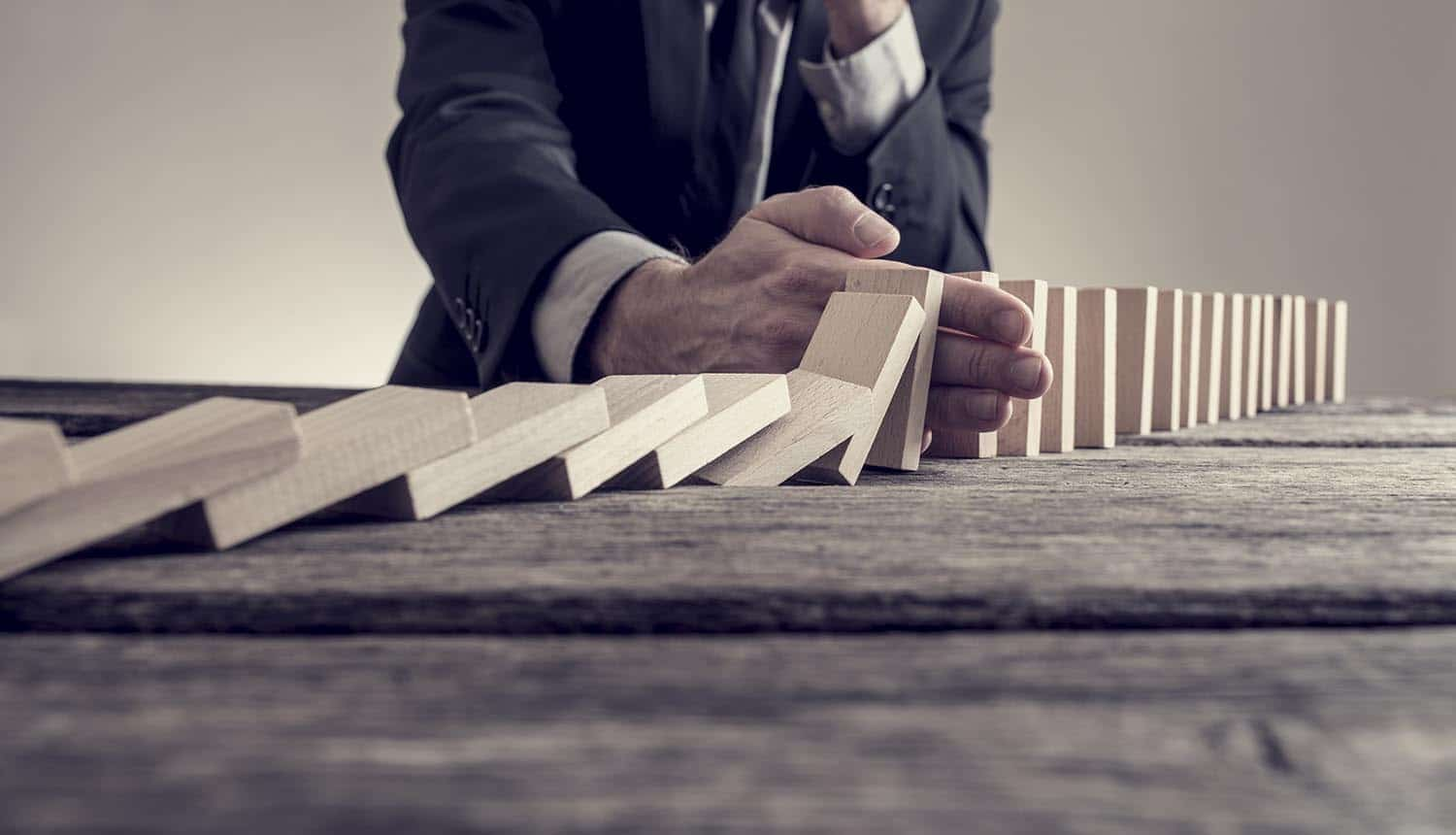 Businessman stopping domino effect on wooden table showing vendor risk management