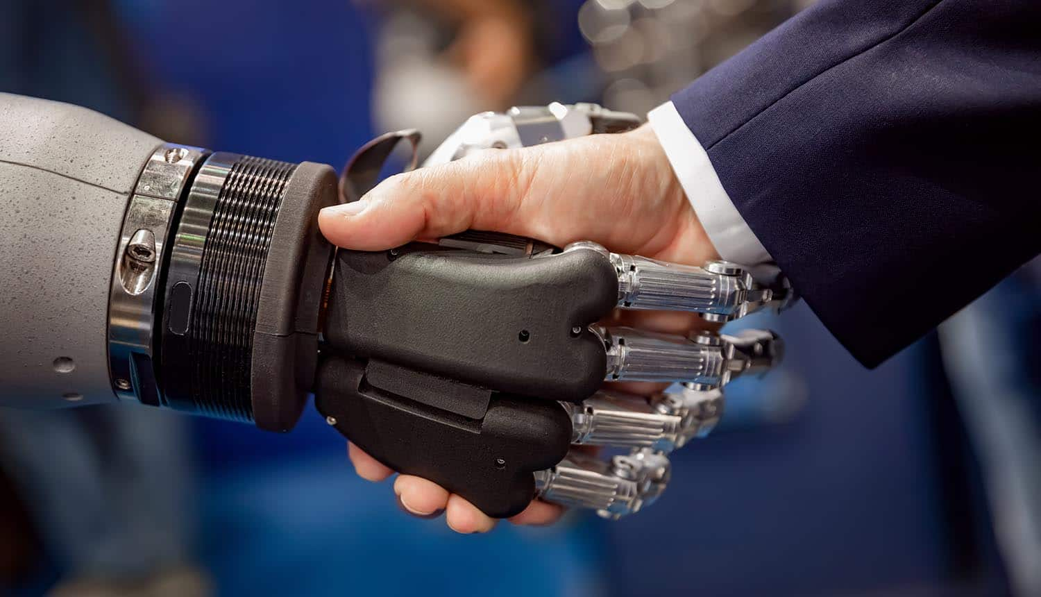 Hand of a businessman shaking hands with a droid robot