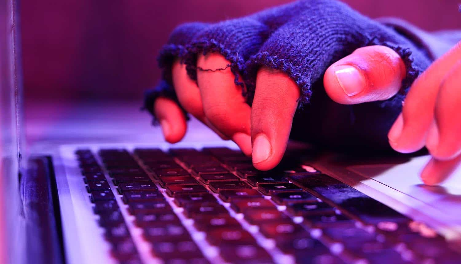 Close up of hacker hand stealing data from laptop showing ransomware attack by LockBit Ransomware gang