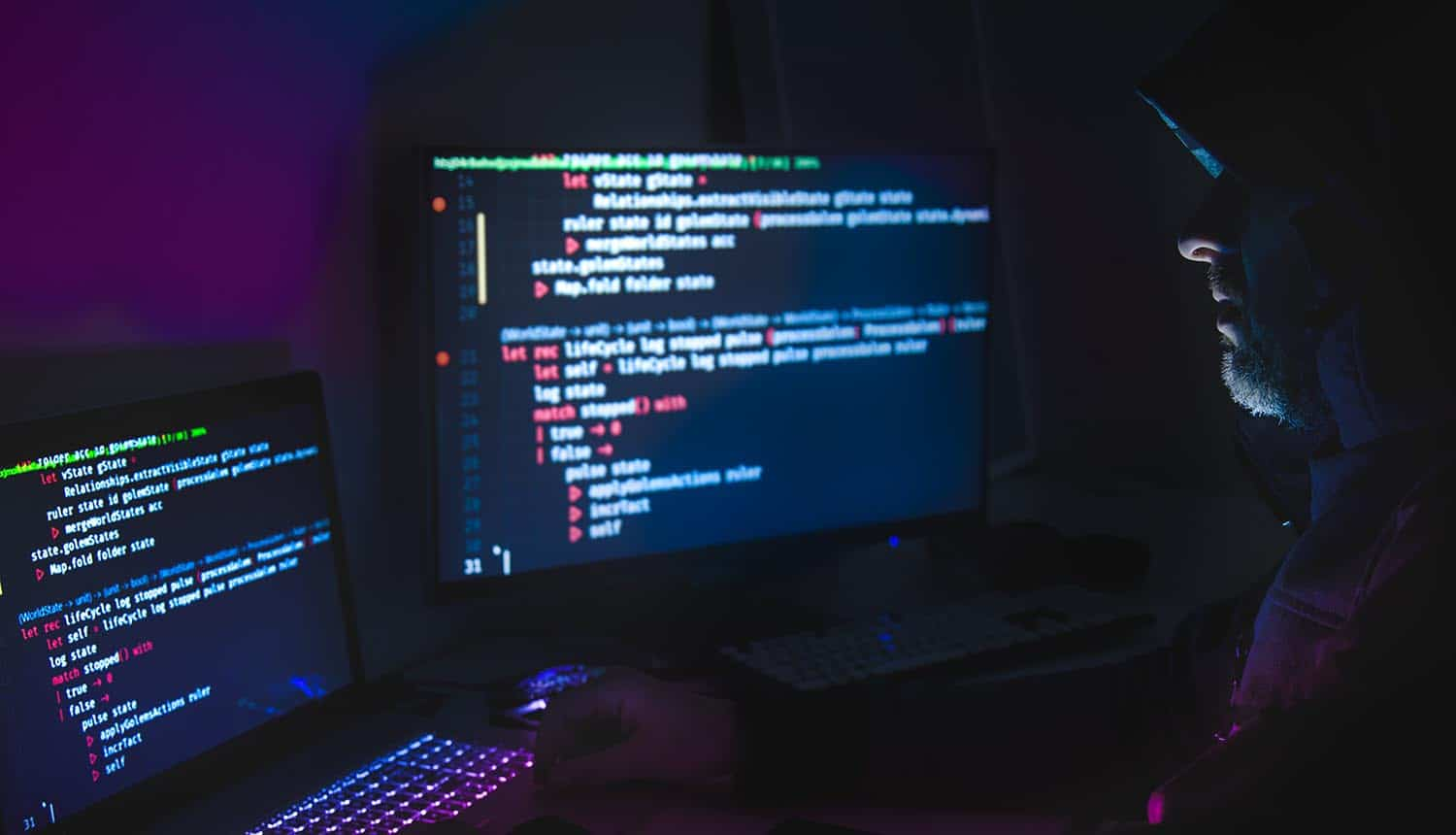 Silhouette of hooded, hacker using laptop showing API security issues