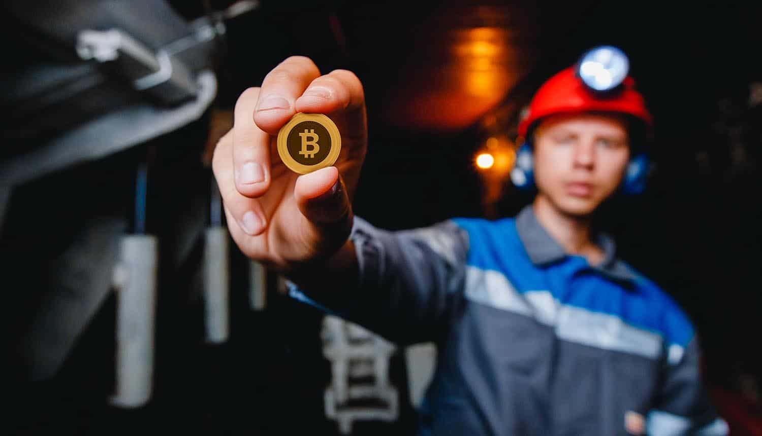 Miner holds a bitcoin in his hand