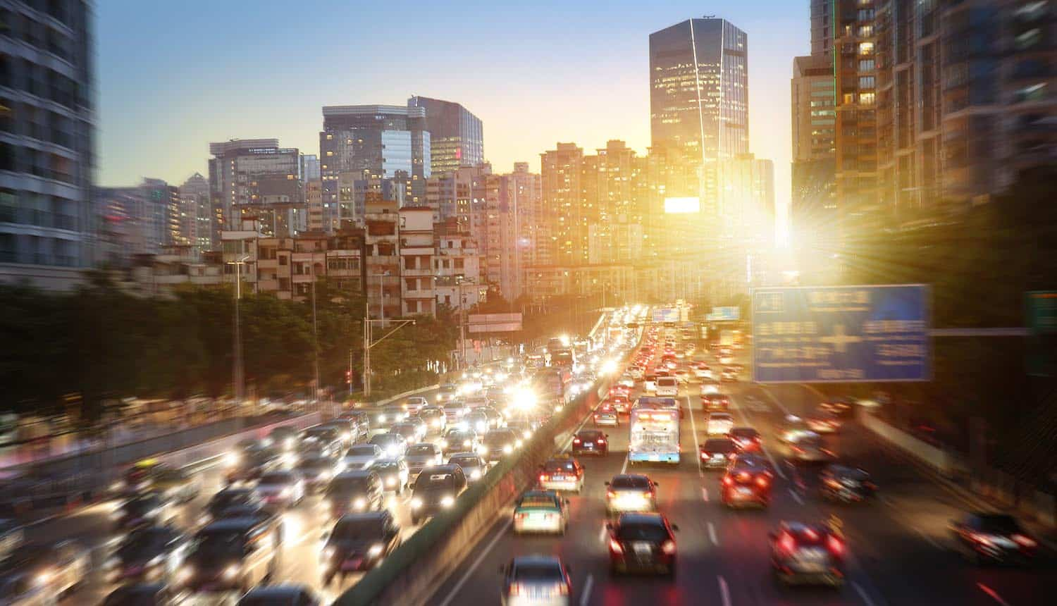 Cars on highway road in busy city showing cybersecurity regulations implication on autonomous vehicles