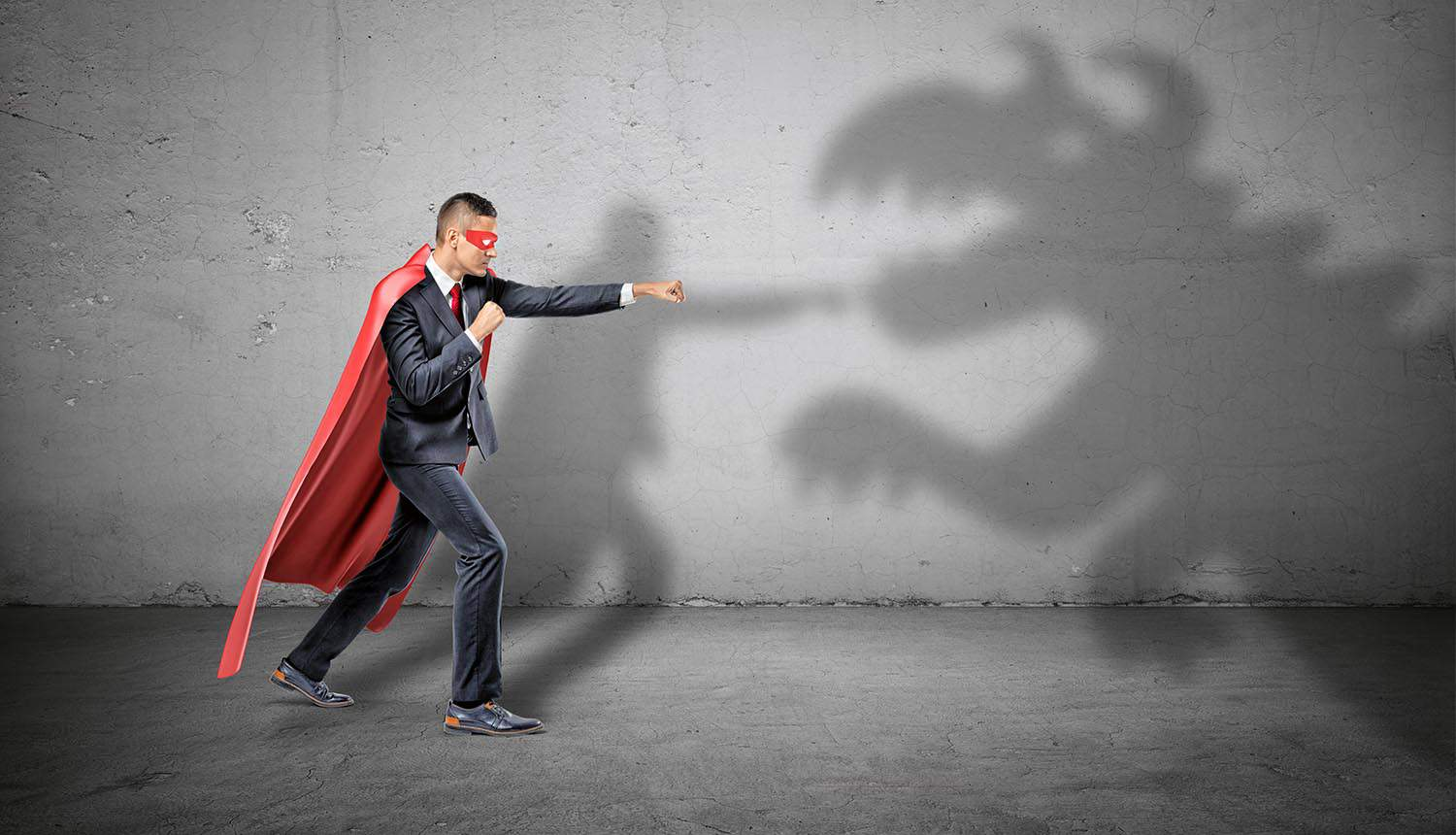 Superhero businessman fighting off a dragon shadow on concrete wall showing cyber resilience to cyber threats