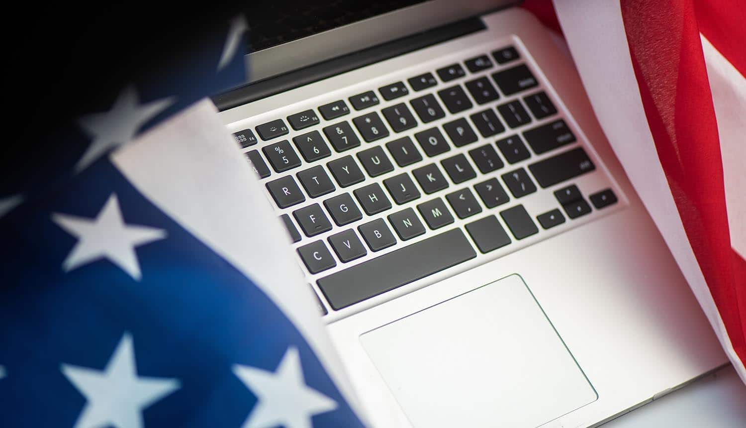 US flag draped around laptop showing senate report revealing federal agencies cybersecurity failures