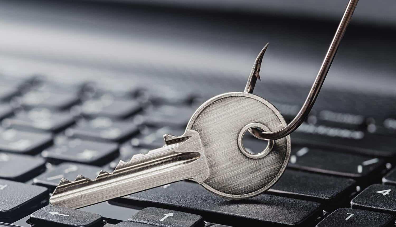 Fishing hook on key on computer keyboard showing increase in phishing during pandemic