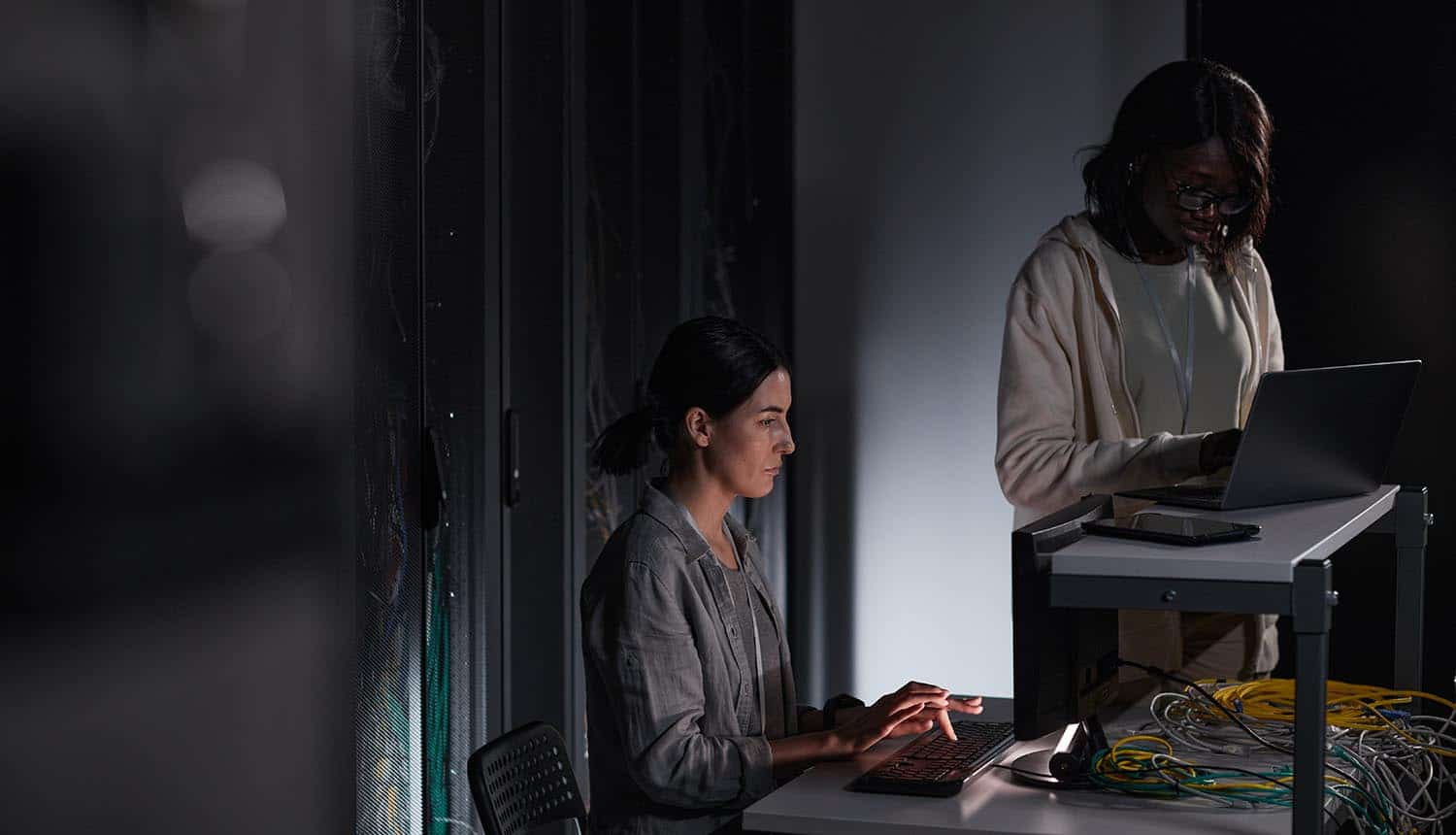 Two female IT engineers working with computer in dark server room showing ransomware solution