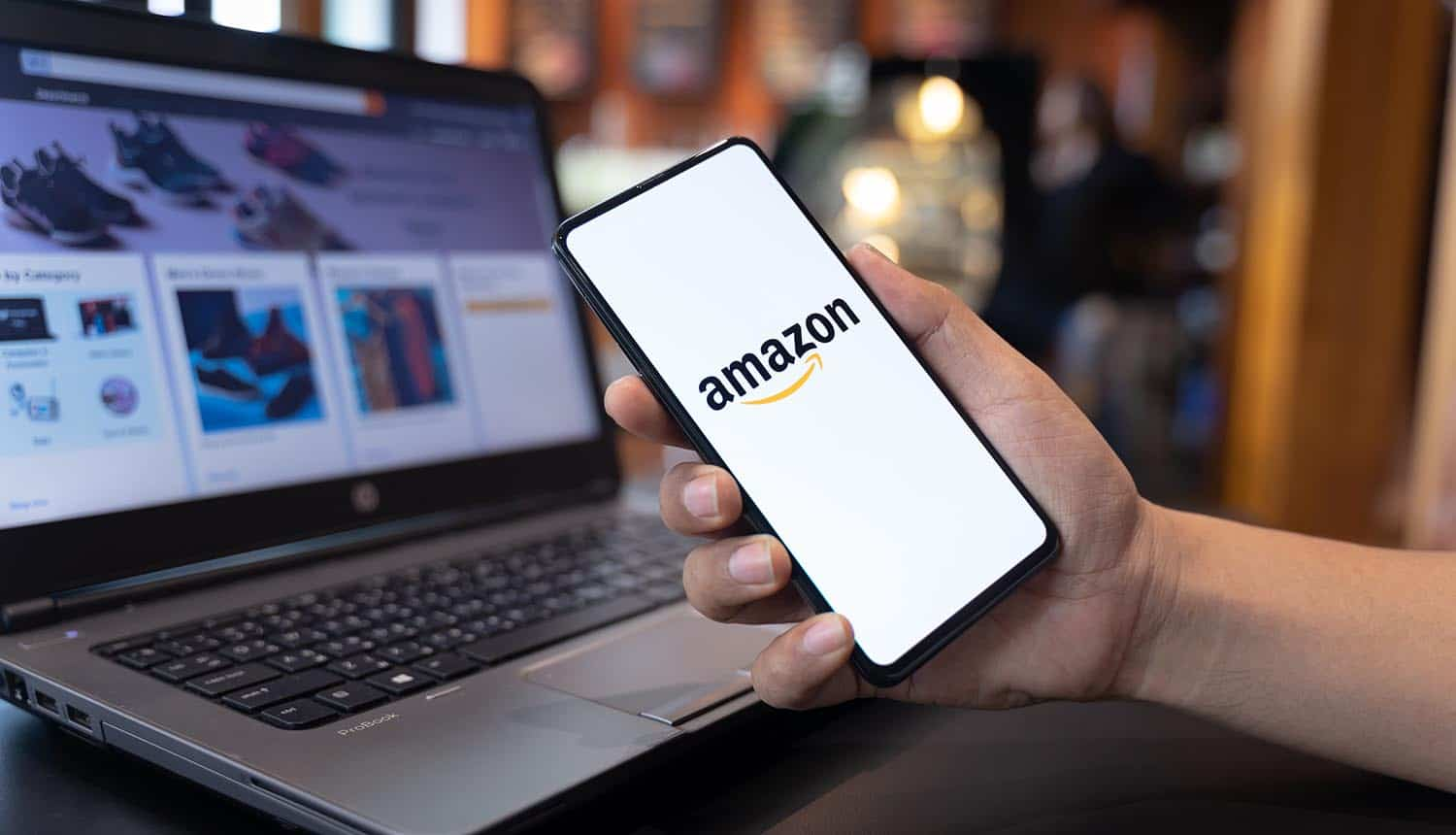 Man hands holding smartphone with Amazon app and laptop showing GDPR fine for targeting advertising