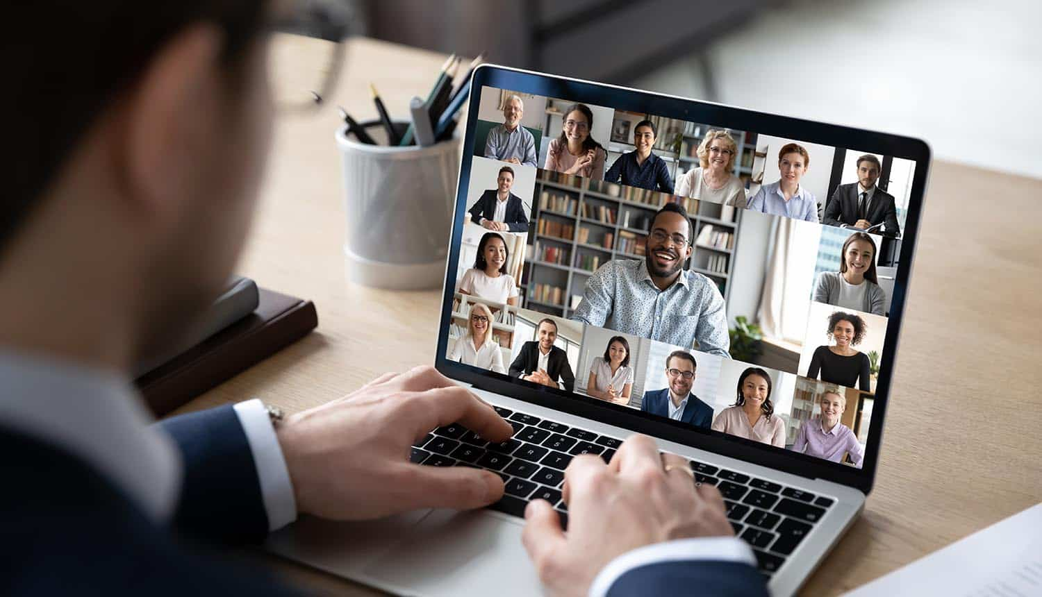 Businessman talking to team of colleagues on online video conference showing hybrid workplace