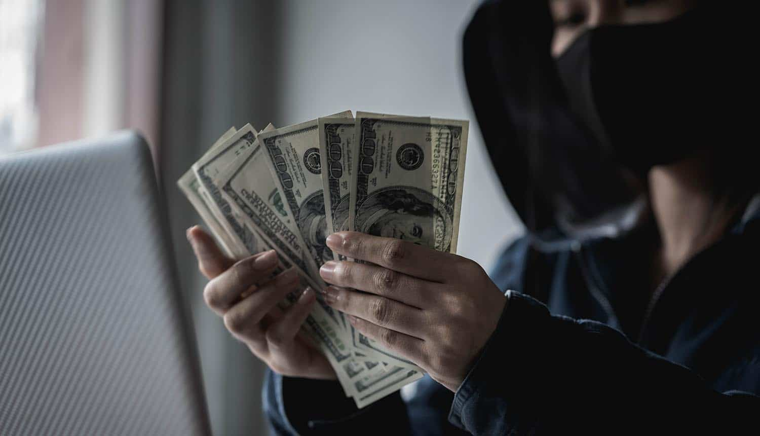 Hacker holding money after successful attack showing ban of ransomware payments