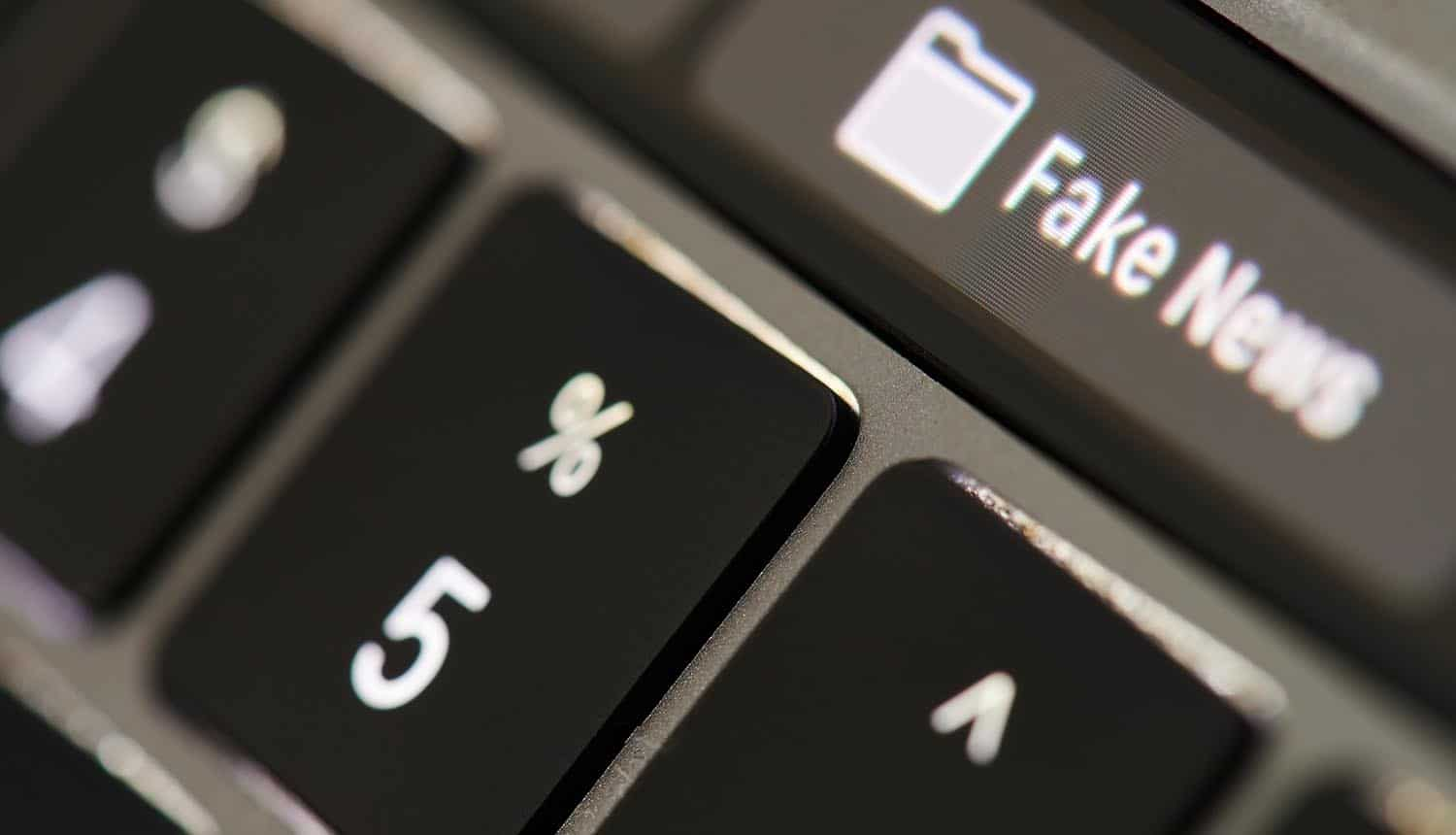 Fake news button on keyboard showing AI and misinformation