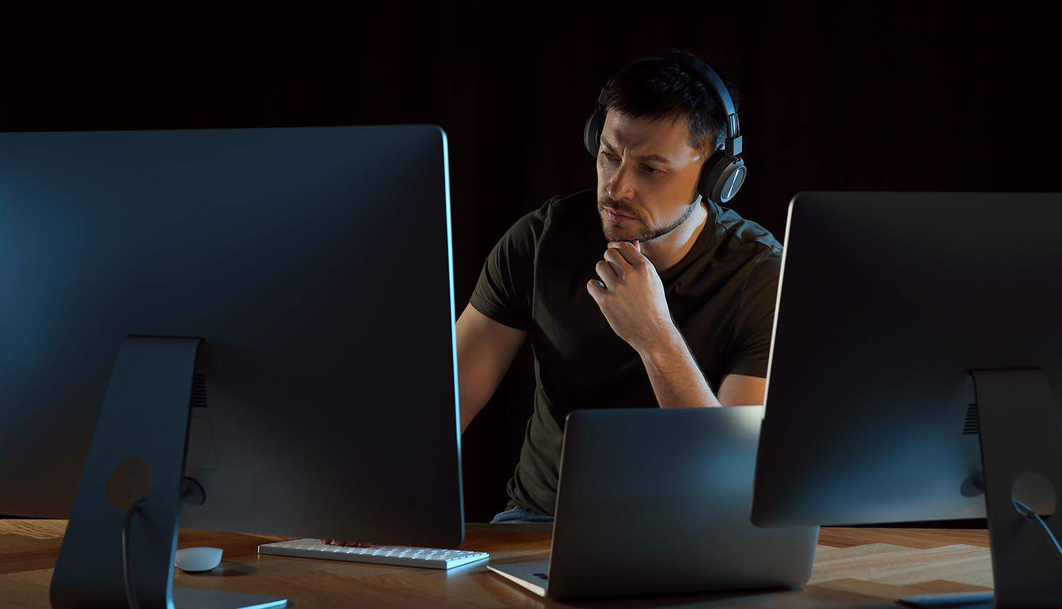 Programmer with headphones working in office at night showing use of devsecops