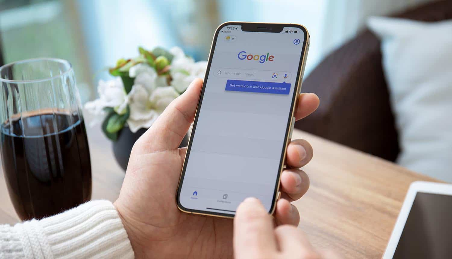 Hand with holding Apple iPhone with Google on screen showing default search engine