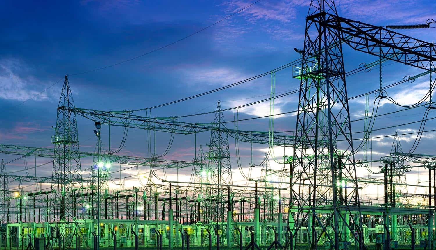 Illuminated electric substation plant at night showing ICS cybersecurity
