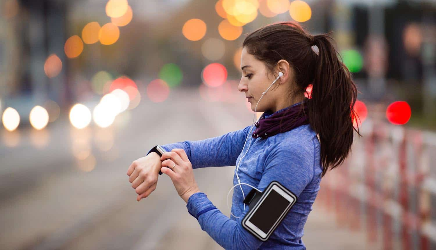 Woman in the city with smartwatch and earphones showing fitness tracking data