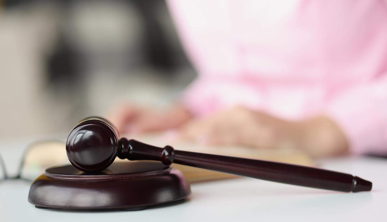 Judge wooden gavel lying on table against background of woman showing challenge of privacy laws