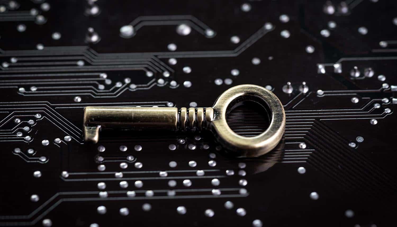Small metal key on computer circuit board showing Ragnarok ransomware master decryptor key