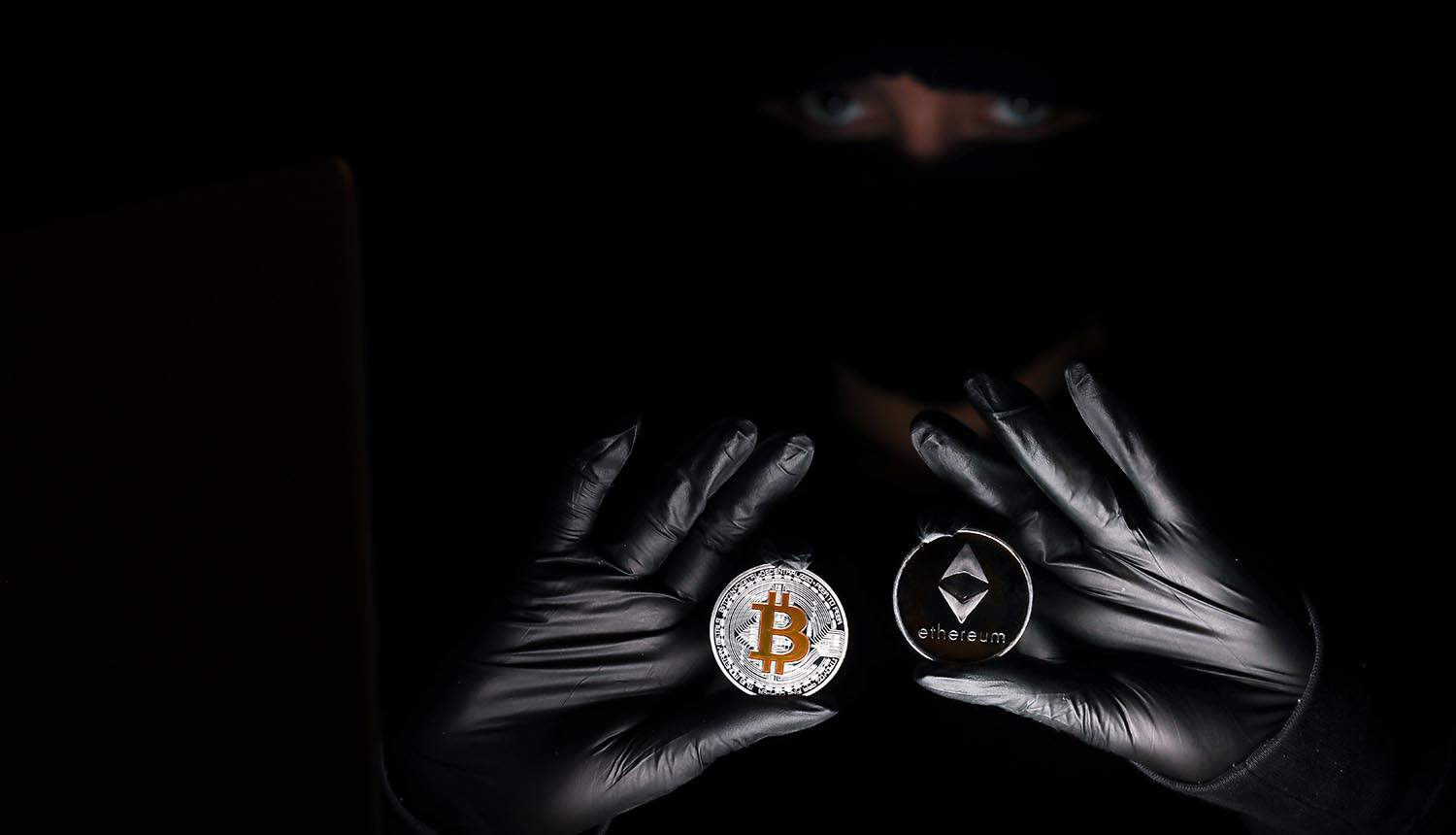 Hacker holding crypto showing crypto exchange sanctioned for ransomware payments