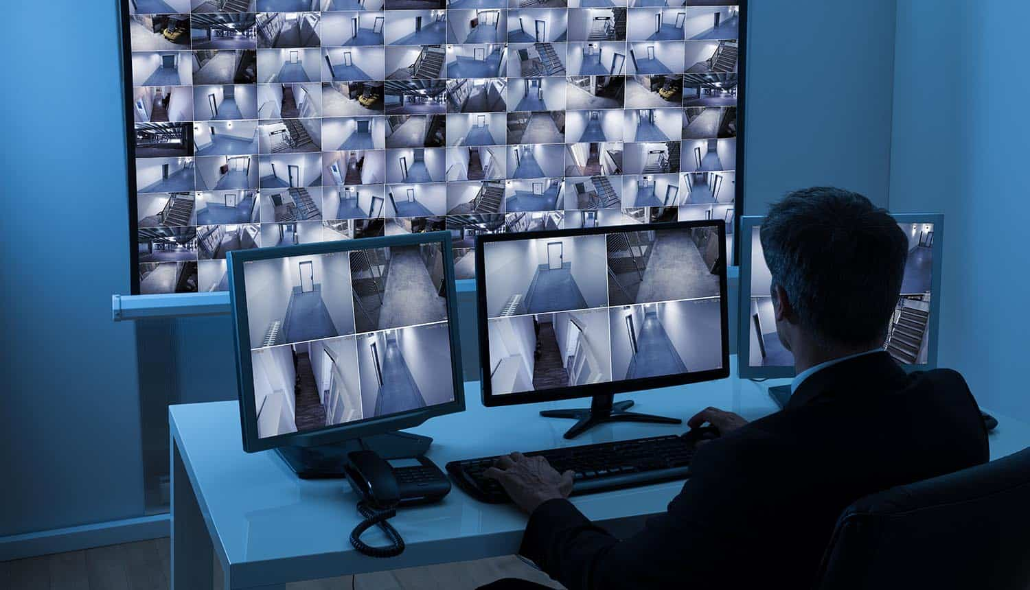 Man in control room monitoring multiple cameras showing cyber-physical security as part of enterprise security