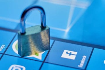 Lock on top of Facebook icon on smartphone screen showing end-to-end encryption