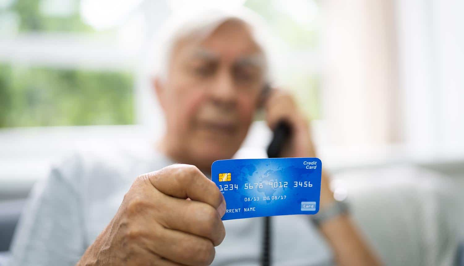 Elderly man holding credit card in scam call showing cost of fraud