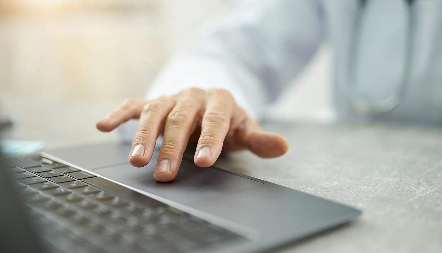 Male doctor hand using modern laptop in clinic showing healthcare organizations need for cyber insurance against ransomware