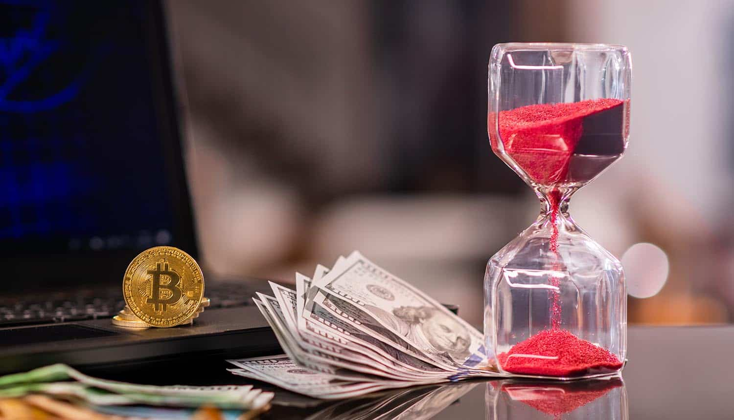 Hour glass and cryptocurrency in front of laptop showing ransomware payments