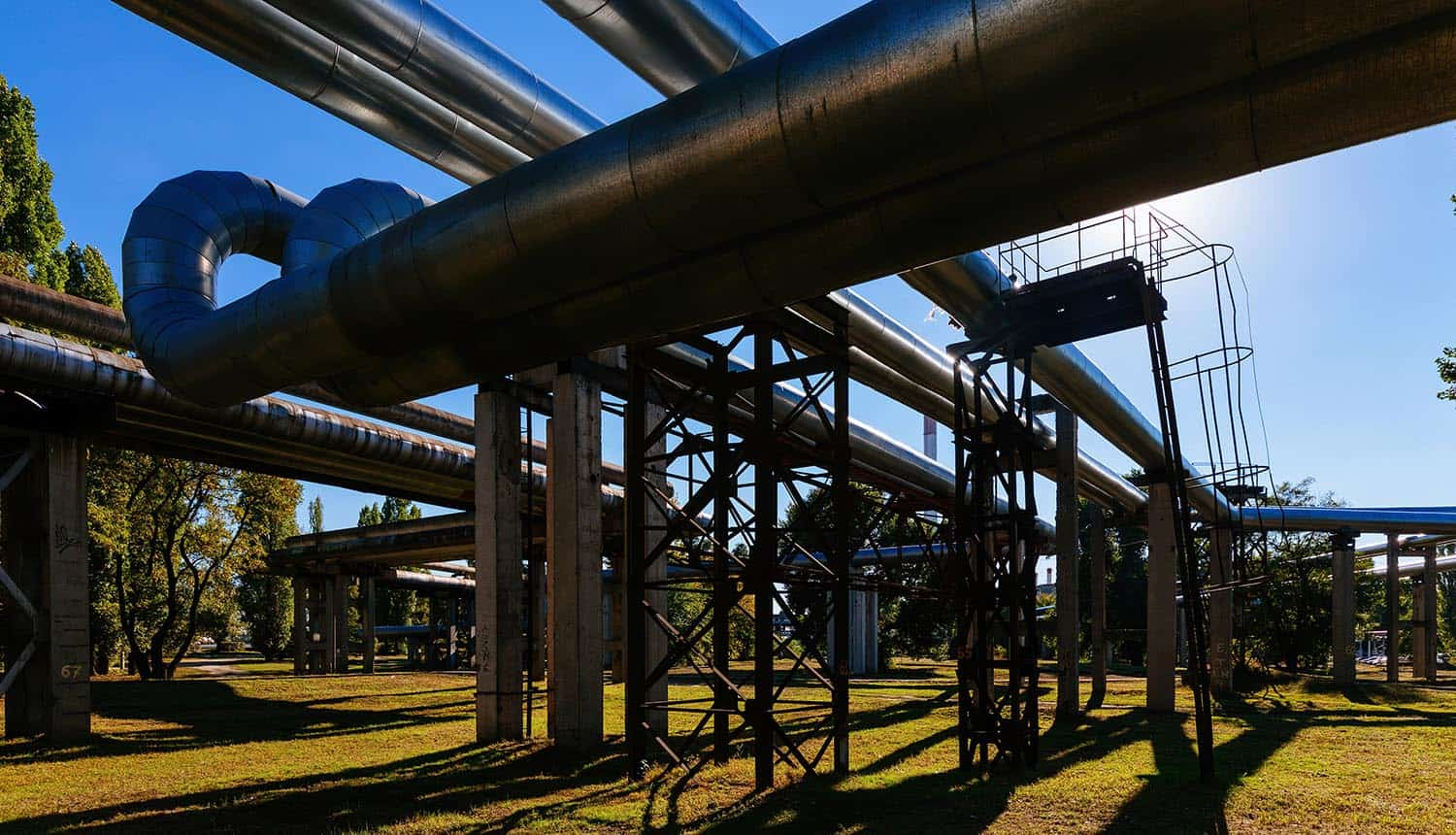 Steel pipelines outgoing from the plant on sunny day showing killware as cybersecurity threat