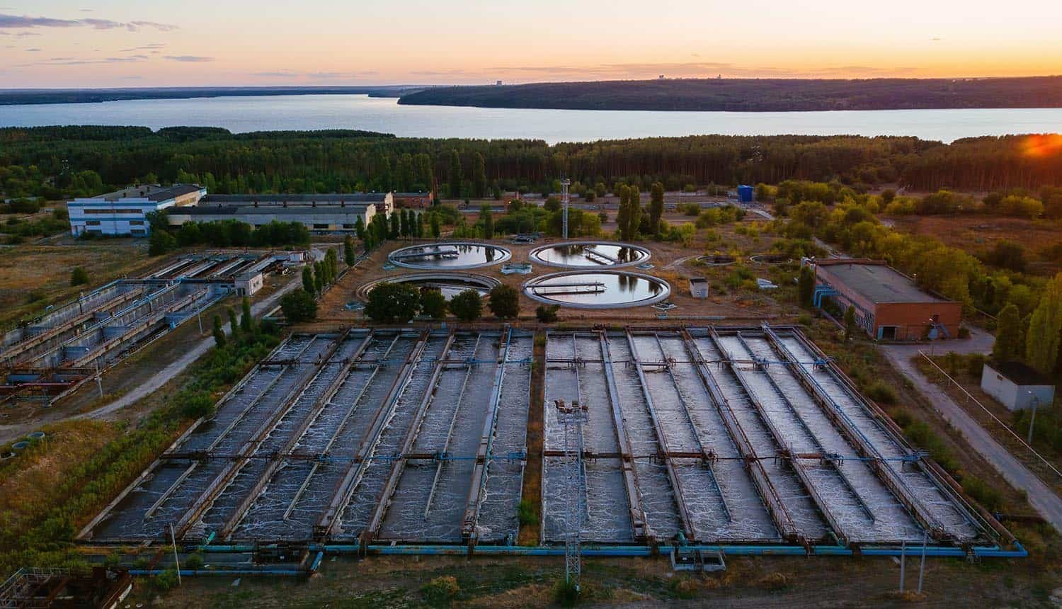 Modern wastewater treatment plant, aerial view at the evening sunset showing cybersecurity advisory on cyber threats on water facilities