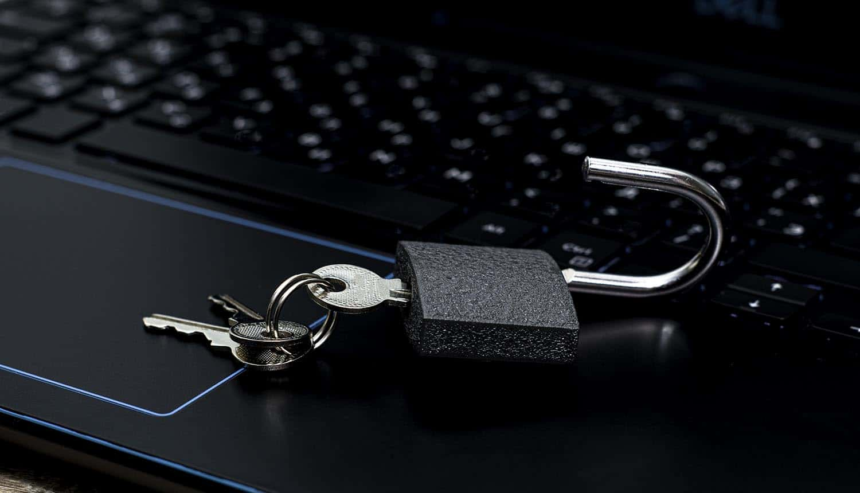 Open padlock with keys on laptop keyboard showing ransomware decryption key