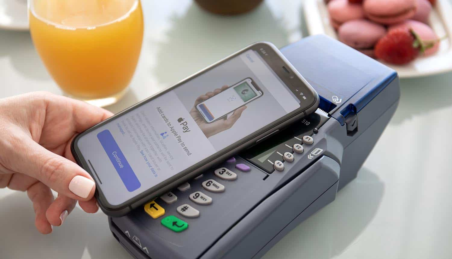 Waman holding iPhone with Apple Pay on the screen showing payment fraud with Visa card