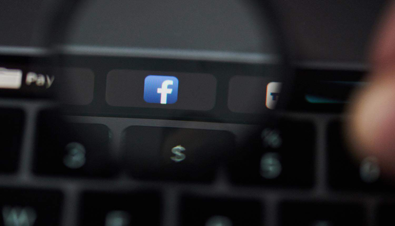 Magnifying glass over facebook button on laptop showing Irish DPC GDPR fine
