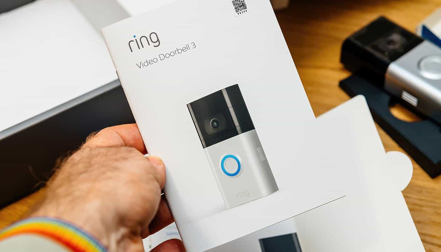 Hand holding instruction manual of Amazon Ring smart doorbell showing invasion of privacy
